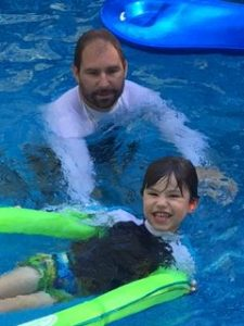 Adult and child in swimming pool.