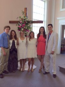 Young Church members in front of sanctuary Easter Cross