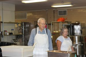 Church volunteers in aprons at Meals on Wheels.