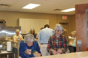 Saturday Servants making sandwiches in the Church kitchen.
