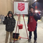 Young men volunteer Red Kettle bell ringers.
